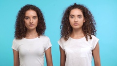 Two young beautiful curly female Caucasian twins in white t-shirts looking at Stock Footage
