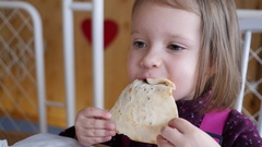 LIttle child girl face portrait funny eat chew a pizza dough piece in restaurant Stock Footage
