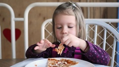 In restaurant pizzeria cute little kid girl portrait eating chewing pizza Stock Footage