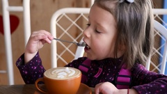 Little kid girl portrait eat a foam from cappuccino latte art with a spoon Stock Footage