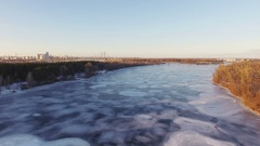 4K Aerial. Fly over frozen winter river in city, sunny day. Stock Footage