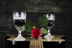 Red Rose and Wine Glasses Resting On Acoustic Guitar With Wooden Background Stock Photos