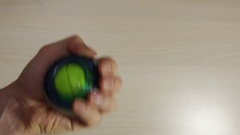 Man rotates the wrist ball, strengthens muscles in hand, fingers, wrist, arm Stock Footage