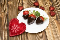 Fresh strawberries dipped in dark chocolate and heart on wooden background Stock Photos