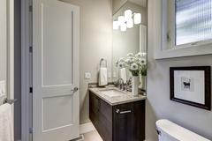 Light gray bathroom interior in luxury home showcases dark wood vanity cabinet  Stock Photos
