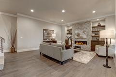 Living room interior in gray and brown colors features gray sofa atop dark hardw Stock Photos
