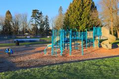 Children playground activities surrounded by green trees at sunrise in Kirkland, Stock Photos