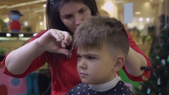 Woman barber cut hair angry upset little boy Stock Footage