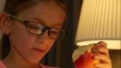 4K Eyeglasses Child Portrait Eating Apple, Girl Face Reading, Studying in Night Stock Footage