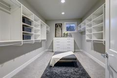 Huge walk-in closet with shelves, drawers and gray bench. Stock Photos
