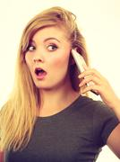 Angry young woman talking on phone Stock Photos