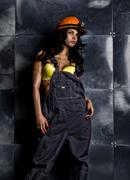 Sexy female miner worker with pickaxe, in coveralls over his naked body Kuvituskuvat