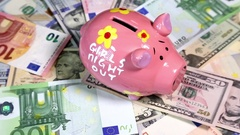 Pink piggy bank on rotating surface with dollars and euro banknotes Stock Footage