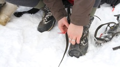 Female tourist putting on ice crampons Stock Footage