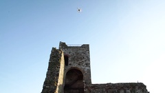 White quadcopter drone landing near medieval walls, 4K Stock Footage