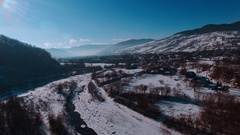 Aerial winter view high above rural village surrounded by pine tree forest Stock Footage