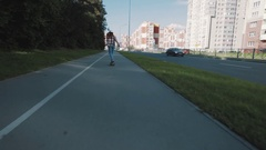 Girl in sunglassesriding longboard on sidewalk at dormitory area on sunny day Stock Footage