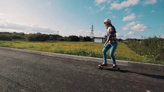 Girl in snapback riding longboard on sidewalk at country side on sunny day Stock Footage