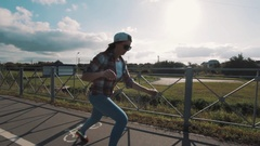 Girl in sunglasses riding longboard on sidewalk at country side on sunny day Stock Footage