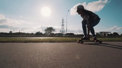 Girl in snapback riding longboard on sidewalk at country road on sunny day Stock Footage