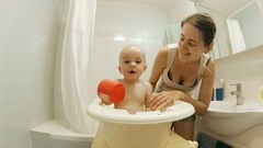 Slow motion of cheerful 1 year old baby boy splashing with mother at bathtub Stock Footage