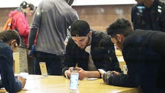 Apple customers boys admiring the latest iPhone smartphone Stock Footage