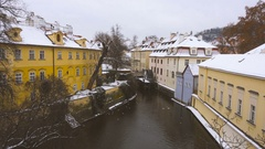 Canal and watermill near Charles Bridge in Prague under the snow in winter Stock Footage