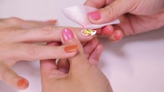 Woman cosmetician wipe nails polish with tissue floral pattern in beauty saloon Stock Footage
