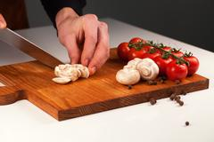 Sliced mushrooms placed on a wooden board with bunch of tomatoes. Dieting and Stock Photos