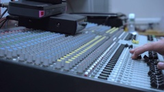Hands of sound engineer work with faders and knobs on professional audio music Stock Footage
