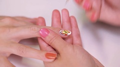 Woman cosmetician painting nails polish orange butterfly in beauty shop Stock Footage