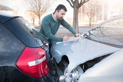 Man writing a car insurance claim after a car crash Kuvituskuvat