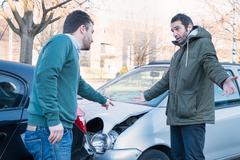 Two men arguing after a car crash accident Kuvituskuvat