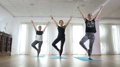 Girls practising balance in tree pose during yoga class at the gym Stock Footage