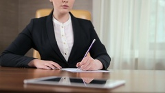 The girl writting on the paper in the office Stock Footage