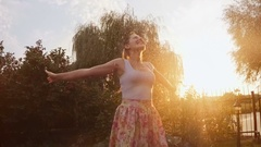Slow motion footage of happy cheerful woman dancing under summer rain at sunset Stock Footage