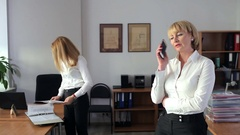 Two women jumping for joy in the office Stock Footage