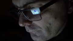 Closeup shot of middle age man in glasses surfing internet at night Stock Footage