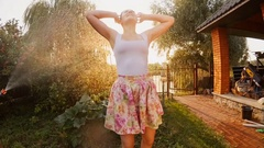 Laughing woman dancing under water flowing from garden hose pipe Stock Footage