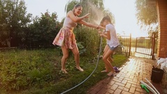 Slow motion video of happy family playing with garden hose at backyard Stock Footage