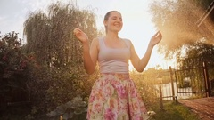 Young girl in wet clothes dancing at garden under water from sprinkler Stock Footage