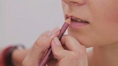 Close up shot. Professional make-up artist applying lips contour Stock Footage