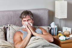 Sick man in bed Stock Photos