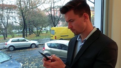 A young, handsome man stands by a window and works on a smartphone, eventually Stock Footage