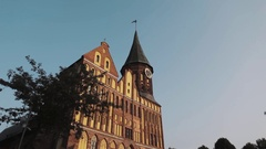Cathedral construction with clock tower in Kaliningrad Kneiphof under summer sky Stock Footage