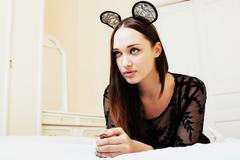Young pretty brunette woman wearing sexy lace mouse ears, laying Stock Photos
