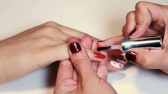 Manicure procedure woman putting transparent polish on painted finger nail Stock Footage
