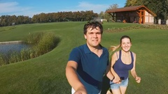 Slow motion footage from camera on selfie stick of couple running and kissing Stock Footage