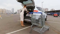 Beautiful young housewife loading car trunk at supermarket Stock Footage