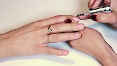 Woman hands brushing plane base polish on finger nails over white surface Stock Footage